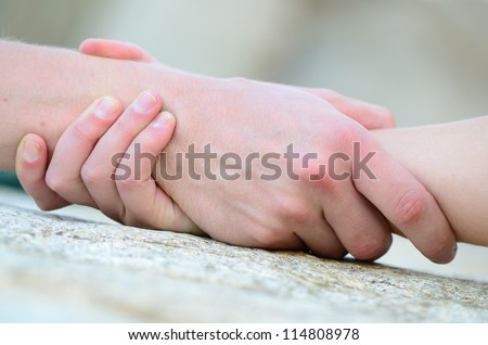 clasped hand for help on a granite rock - stock photo