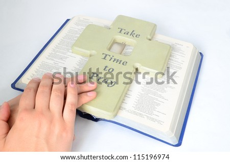 clasped hands for pray on a bible - stock photo
