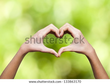 clasped hands forming a heart with natural background - stock photo