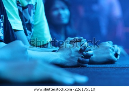 Clasped hands in Blue spotlights - stock photo