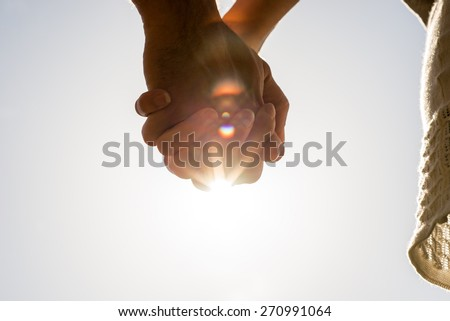 Clasped hands of a young romantic man and woman against a bright sun flare with copyspace, conceptual image of love and friendship. - stock photo