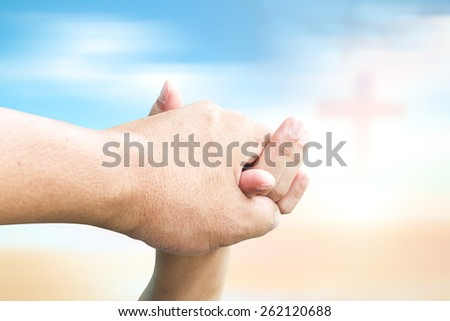 Clasping hand over blurred the cross on sunset background. - stock photo