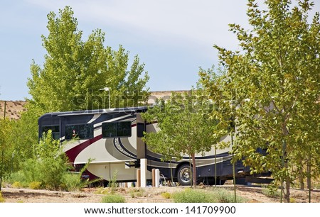 Class A Diesel Pusher RV ( Motorhome ) - Recreational Vehicle Between Trees in One of Arizona RV Parks. Traveling Photo Collection. - stock photo