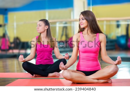 Class and instructor doing stretching pilate exercises in fitness studio - stock photo