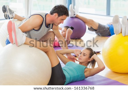 Class exercising with fitness balls as trainer helps one at a bright gym - stock photo