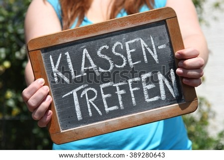 class meeting written in German language on writing slate shown by young female (translation: class meeting)