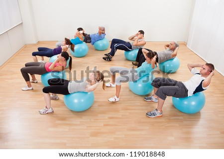 Class of diverse people doing pilates exercises in a gym doing head lifts to strengthen their abdominal muscles - stock photo