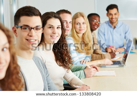 Class of many smiling students in a university - stock photo