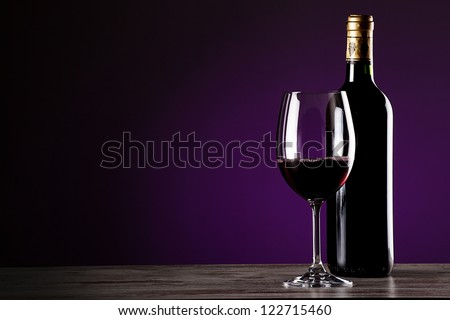 class of wine and bottle on wooden table