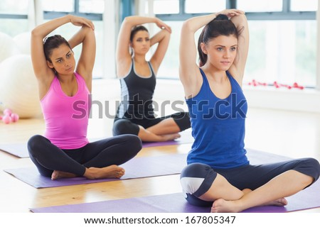 Class stretching hands behind heads on mats at yoga class in fitness studio