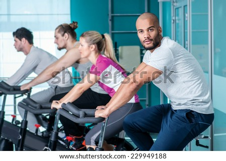 Classes at the gym. Young boy sitting on a stationary bike and looks at the camera while his three friends pedal in the gym - stock photo