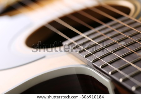 Classic acoustic guitar at weird and unusual perspective closeup. Six strings, free frets, sound hole and soundboard. Musical instruments shop or learning school concept