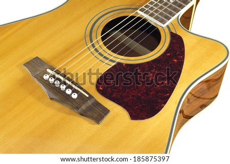 Classic acoustic guitar natural color top fragment with six strings isolated on white closeup