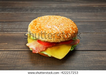 Classic american burger fast food. Big double cheese burger with bacon at wood. Hamburger with fresh vegetables and meat. Burger with beef, tomato, lettuce. Cheeseburger at rustic wooden background.