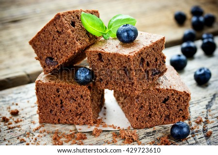 Classic American dessert chocolate brownie with blueberry on wooden table selective focus - stock photo