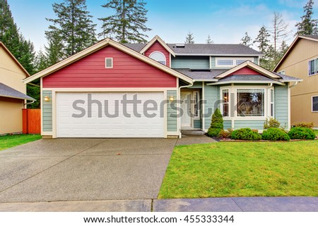 Classic American house with red and blue trim. Also garage with driveway and well kept lawn around