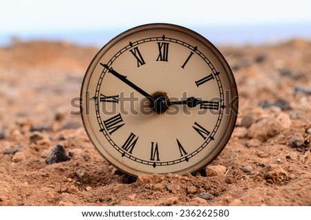 Classic Analog Clock In The Sand On The Rock Desert - stock photo