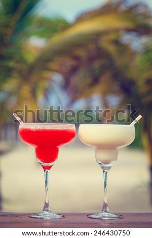 Classic and strawberry margarita cocktails on tropical sand beach - stock photo