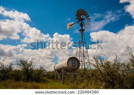 Classic antique Farm Windmill with clouds surrounding it. - stock photo