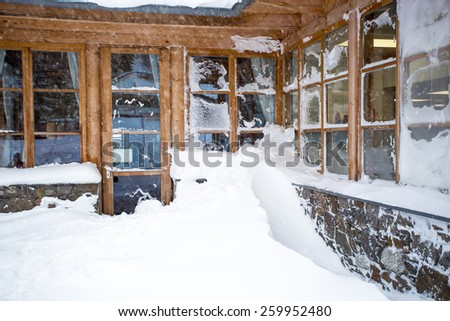 Classic Austrian wooden house with big windows covered by snow at snowstorm - stock photo