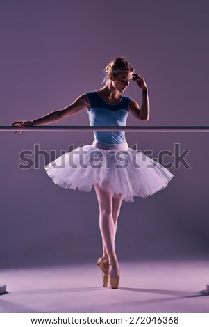 classic ballet dancer in white tutu at ballet barre on a lilac background - stock photo