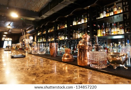 Classic bar counter with bottles in blurred background - stock photo