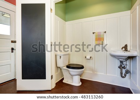 Classic bathroom interior with toilet and sink. Also green and white walls. Northwest, USA