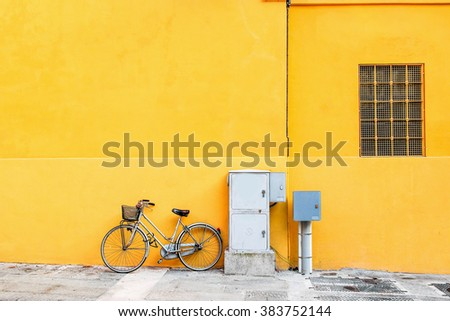 Classic bicycle standing over wide yellow wall. - stock photo