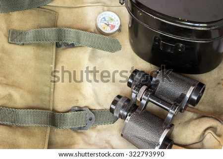 Classic binoculars and compass with army food container on green rucksack