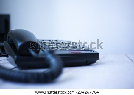 Classic black land line telephone on wooden desk. Selective focus with shallow depth of field. - stock photo