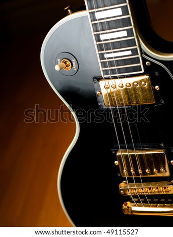 Classic black rock and roll or jazz guitar in soft spotlight. Stage or studio concept ready to perform.