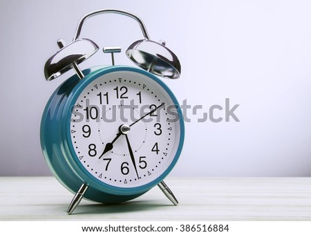 classic blue alarm clock morning wake-up time - stock photo