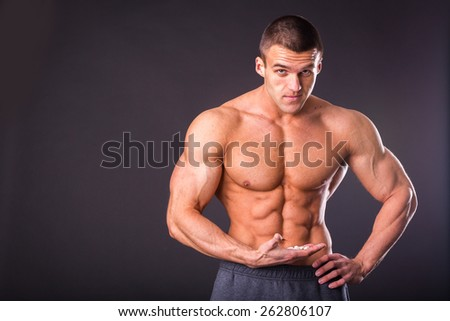 Classic bodybuilder, posing on a black background. Athletic man showing his muscle in suspense. Sports, strength, bodybuilding, physical strength.