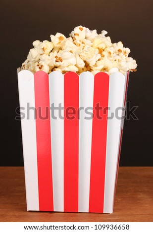 classic box of popcorn on wooden table on brown background