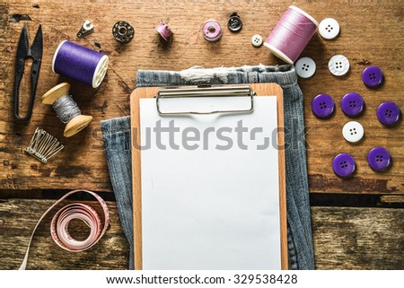 Classic brown clipboard and blank white paper with Sewing tools on grunge wood background - stock photo