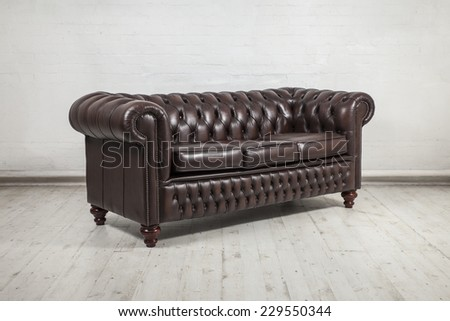 classic brown leather sofa against painted white brick wall - stock photo