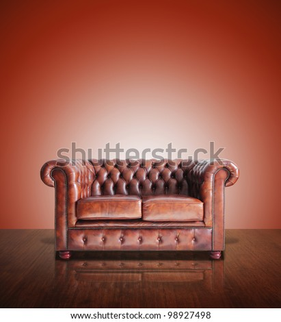 Classic Brown leather sofa and old red wood background.