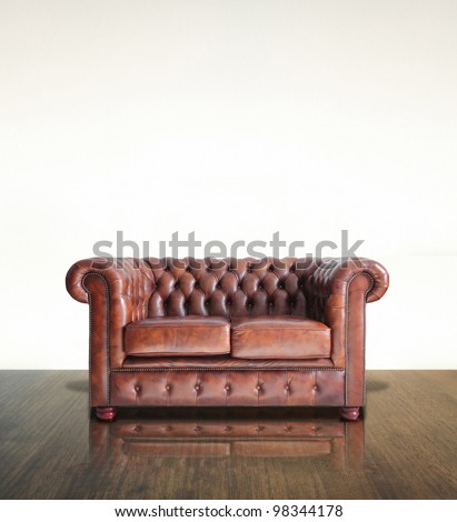 Classic Brown leather sofa and old wood background. - stock photo