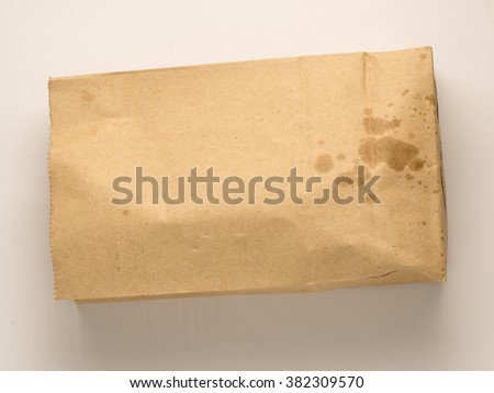 classic brown paper lunch bag with grease spots isolated on white background