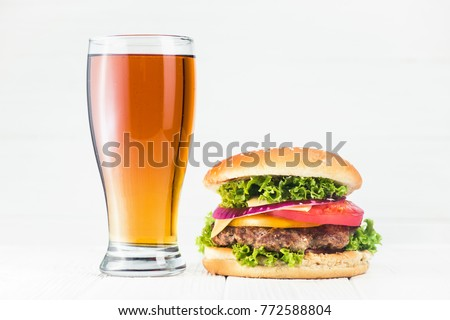 Classic burger and beer glass on wood white table