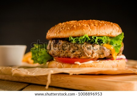 Classic burger with tasty beef, salad, sauce and tomato on dark background. American food