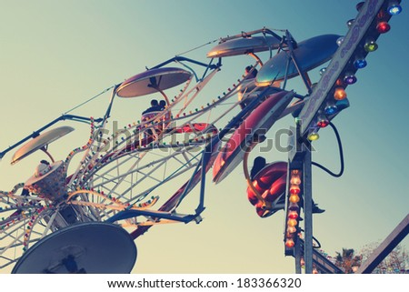 Classic carnival ride in subtle vintage retro tones - stock photo