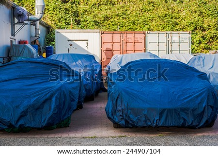 Classic Cars wrapped for restoring with covering sheet in garage Various Classic Cars wrapped for restoring with covering sheet outside of auto repair shop - stock photo