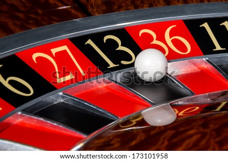 Classic casino roulette wheel with black sector thirteen 13 and white ball and sectors 6, 27, 36, 11 - stock photo