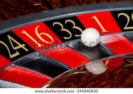 Classic casino roulette wheel with black sector thirty-three 33 and white ball and sectors 24, 16, 1, 20 - stock photo