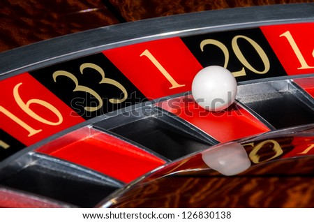 Classic casino roulette wheel with red sector one 1 and white ball and sectors 16, 33, 20, 14 - stock photo