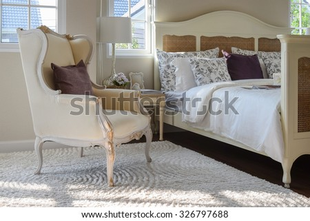 classic chair with brown pillow on carpet in vintage style bedroom interior - stock photo
