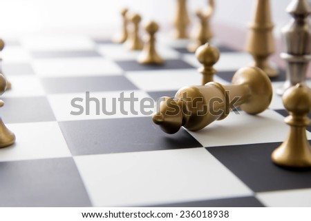 Classic chess game - fallen gold king on chessboard