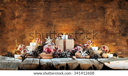 Classic Christmas Composition. Box with Candles, Balls, Toys, Pine Cones, Walnuts on Wooden Background - stock photo