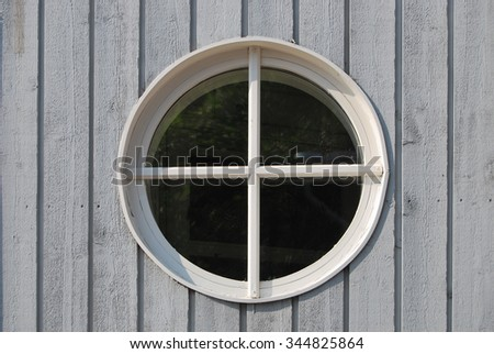 Classic circular window in rough wooden plank wall - stock photo